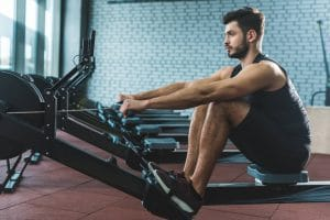 Young sportsman doing exercise on rowing machine - Fitness Expo
