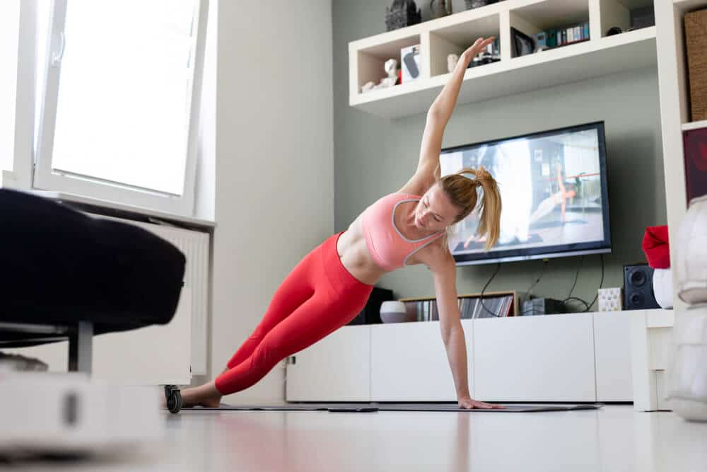 Attractive sporty woman working out at home | Fitness Expo
