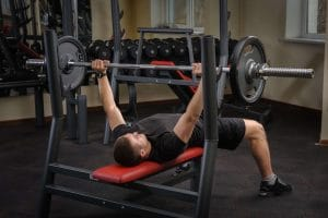 man lifting a barbell in a training bench - Fitness Expo