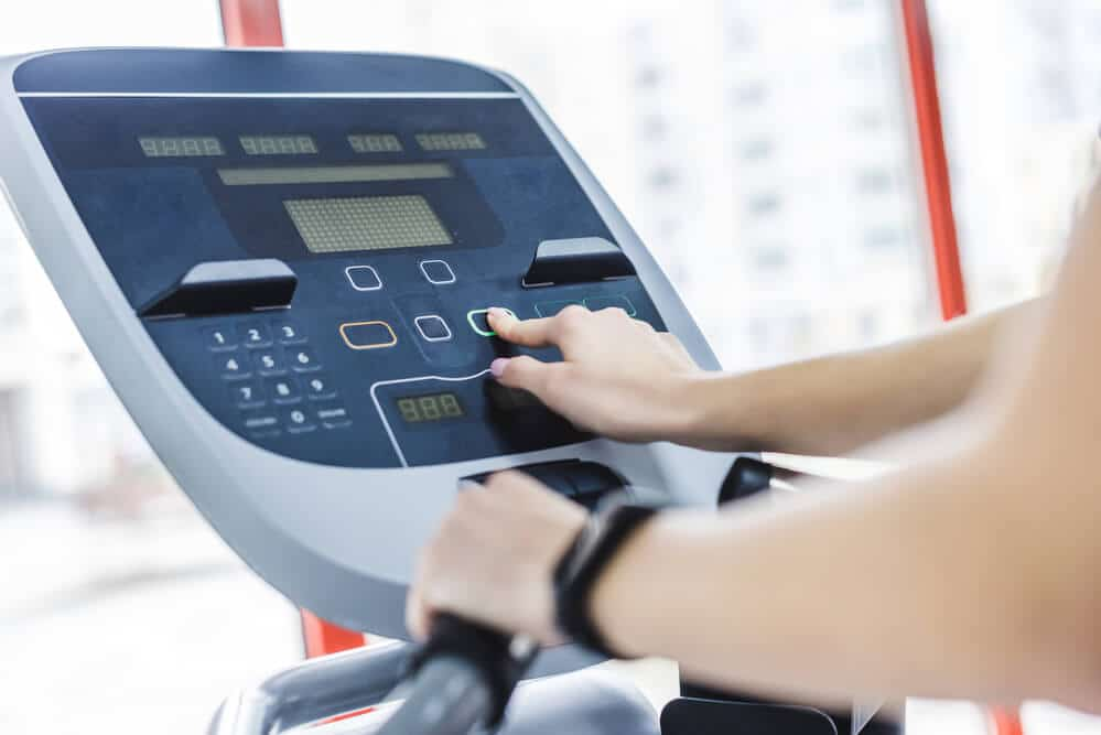 woman changing the settings of elliptical machine