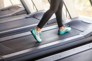 Female runner legs on racetrack in gym - Fitness Expo