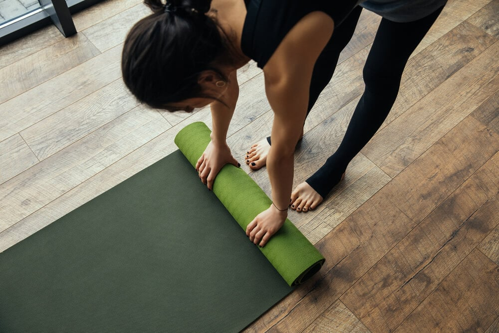 girl putting yoga mat on floor - Fitness Expo