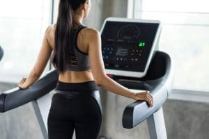 Woman walk and run on treadmills in gym - Fitness Expo